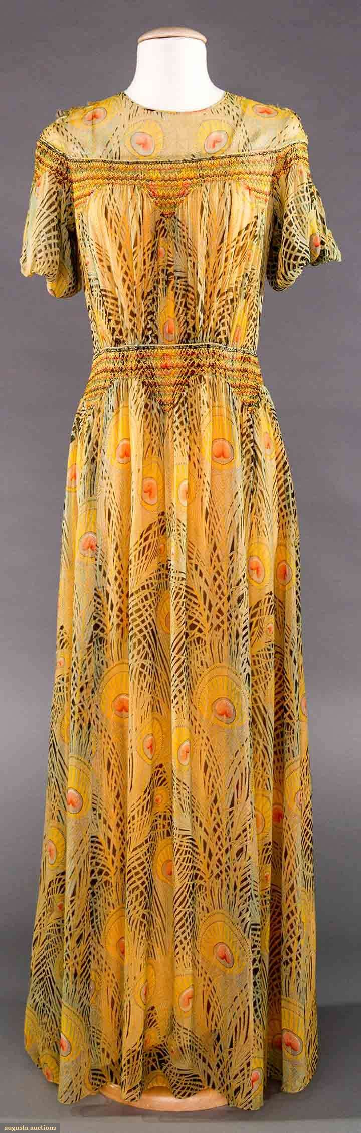 "LIBERTY PRINTED CHIFFON DRESS, LONDON, 1930s. 2017 Spring Augusta Auctions. Labeled ""Liberty & Co."" dress in signature peacock feather print, colorful smocking above bust & at midriff, short puff sleeves, original peach silk slip w/ peacock print spaghetti straps"