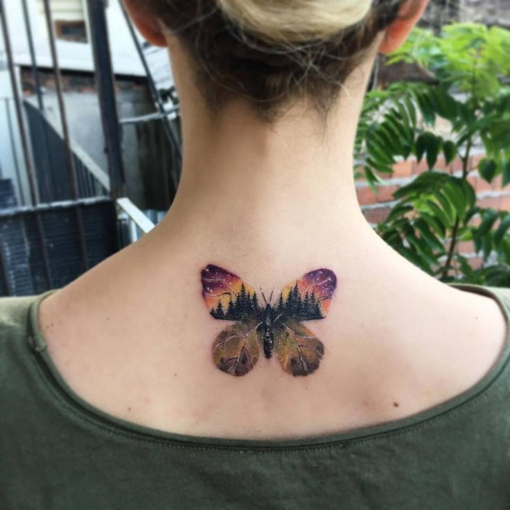 Double exposure butterfly tattoo on the upper back.
