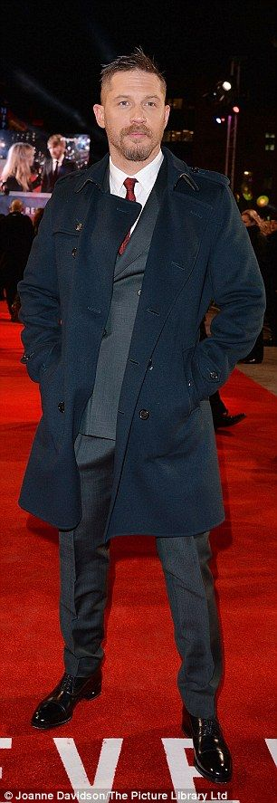 Playing it cool: Tom Hardy put on a stylish display in a sophisticated navy winter coat over his grey Burberry suit