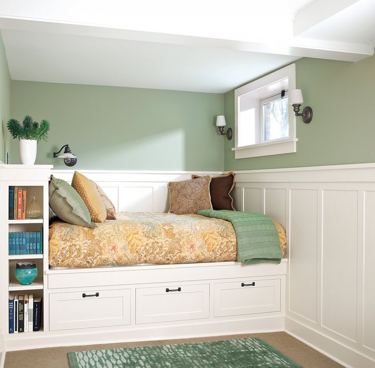 a basement living area with bed over a built-in storage area