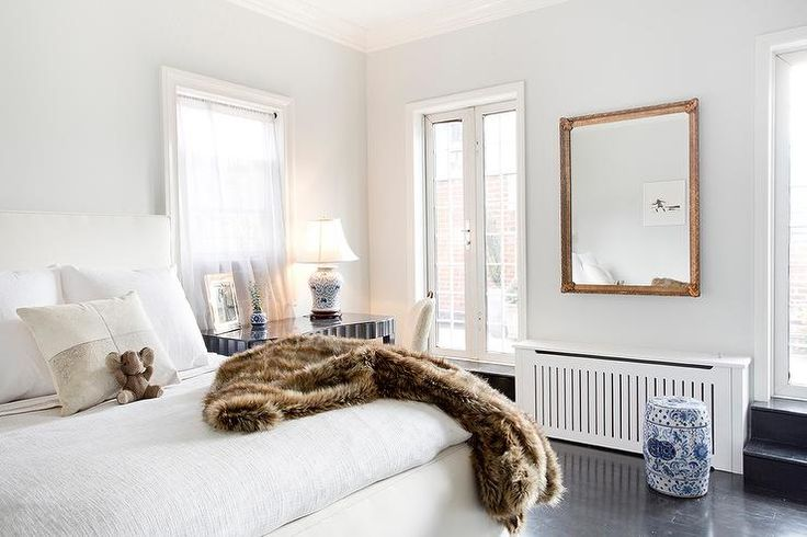 A gilt mirror, mounted on a pale gray wall between glass front patio doors, reflects a white upholstered bed dressed in white bedding and topped with a brown faux fur throw blanket.