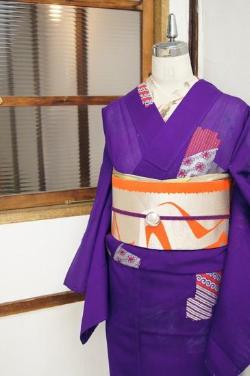 綺麗な紫色の地に、ぐるぐる渦巻きやストライプ、キュートなお花がデザインされた絵カルタのような装飾模様が散らされた、レトロモダンな紗の夏着物です。