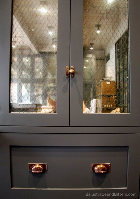 matte grey cabinets, antiqued chicken wire mirror, copper (?) hardware, latches and pulls