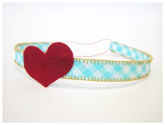 Faixa de cabelo infantil feita com aplique de feltro em formato de coração, tecido 100% algodão xadrez turquesa e  ponto caseado ocre. Elástico ajustável traz conforto e faz com que a faixa acompanhe o crescimento do bebê. R$35,00