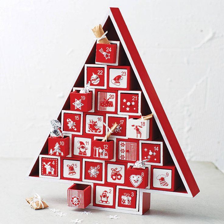 A gorgeous wooden Nordic style advent calendar with twenty four drawers stacked…