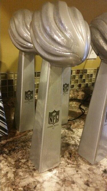 Lombardi trophy centerpieces we made using 99 cent store vases ... Foam footballs ... spray paint snd stickers