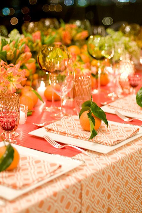 Orange, pink and green color scheme with oranges at each place setting for a colorful summer party.