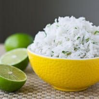 Bowl of delicious cilantro lime rice served in a yellow bowl with three lime halves next to the bowl.