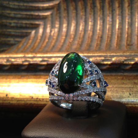 Кольцо с турмалином белое золото : шинка данного кольца сделана из золотого узора покрытого белыми бриллиантами. В этот узор гармонично вплетены синие сапфиры. Венчает всю эту красоту великолепный турмалин зеленого цвета, овальной формы огранки кабошон. Этот природный камень придает шарм всему кольцу. Это кольцо подойдет тем, кто не просто хочет показать свой достаток но и носить модное и красивое украшение.кольцо золото бриллиант
