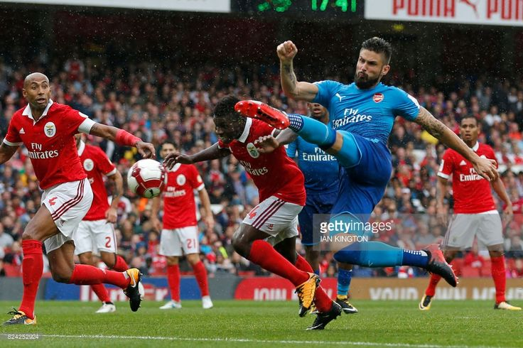 TOPSHOT - Arsenal's French striker Olivier Giroud (R) shoots to score their fouth goal during the pre-season friendly football match between Arsenal and Benfica at The Emirates Stadium in north London on July 29, 2017, the game is one of four matches played over two days for the Emirates Cup. / AFP PHOTO / Ian KINGTON / RESTRICTED TO EDITORIAL USE. No use with unauthorized audio, video, data, fixture lists, club/league logos or 'live' services. Online in-match use limited to 75 images, no…