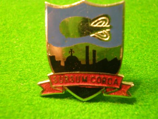 National service badge.  Evocative national service badge featuring London skyline overflown by a barrage balloon. This trademark was used by P.B.Cow Ltd a rubber and plastics company that produced barrage balloons. They had factories in Streatham and Stanmore. Very bright chrome and enamel with half moon button hole fixing made by Thos. Fattorini, B\'ham.