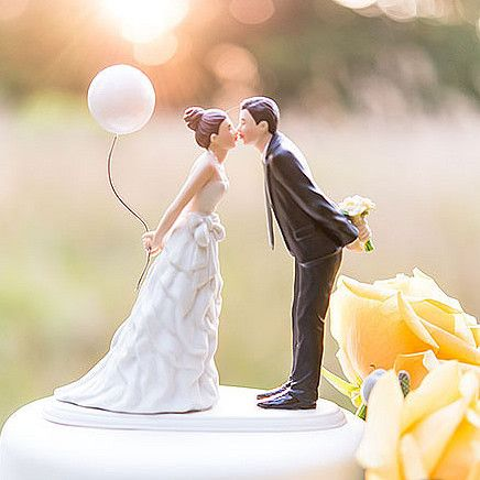This couple is sweetly leaning forward for a kiss as husband and wife! Wearing a beautiful bowed dress and clasping a balloon, this beautiful bride is leaning towards her one true love as he holds ont