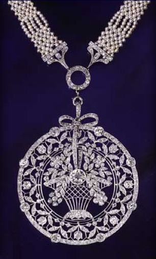 """Platinum millegrain and diamond fittings attached to an openwork platinum millegrain circular pendant, outlined by a diamond border. This encloses a tall basket of diamond flowers centred on a collet diamond, and joined to the necklace by a ribbon tied into a bow, and surrounded by an openwork garland of flowers and leaves on """"knife-edge"""" wires. C. 1910"""