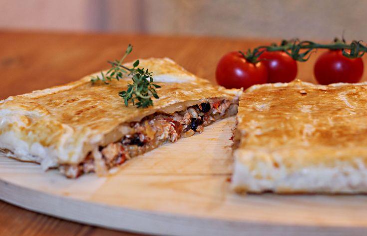 Auf einem Holzbrettchen liegt eine andalusische Blätterteigpastete namens Pastela moruna. Sie ist in der Mitte durchgeschnitten und gibt den Blick frei auf eine Füllung aus Hühnchenfleisch, Mandeln und Rosinen.