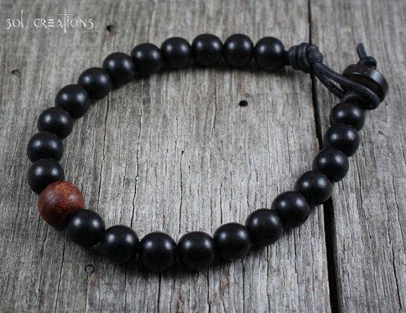 Bracelet homme en cuir de perles mala. Cette pièce se compose de perles en bois ébène (8mm), une perle centrale en bois rouge et une perle fermoir en bois de coco, enfilées sur un cuir marron durable de haute qualité. Bois d'Ebène est principalement noir avec des notes légères de brun foncé ici et là. J'utilise une perle et boucle fermoir de style qui est sécurisé et garanti pour rester fermé. Doit être robuste, indémodable et durable... comme bracelet d'un homme.  J'utilise seulement la…