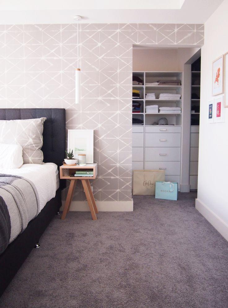 Bedroom with custom wallpaper in Scandinavian style. Walk in wardrobe and scandi bedside tables