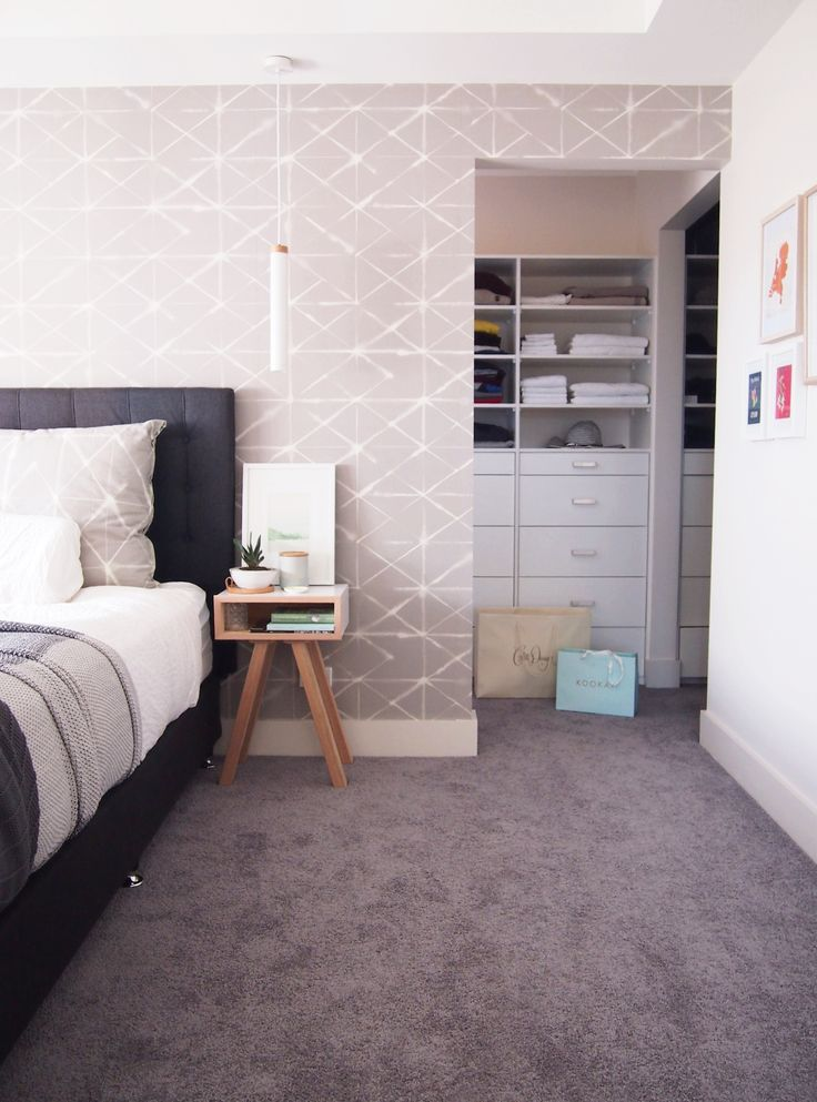 Bedroom with custom wallpaper in Scandinavian style. Walk in wardrobe and scandi bedside tables
