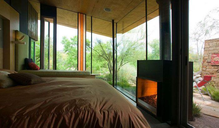 Спальня может похвастаться огромными окнами, превратившимися в стеклянные стены. Двухсторонний камин лишь усиливает производимый эффект, к тому же он ещё создаёт уютную атмосферу на террасе, где можно отдохнуть прохладными вечерами.