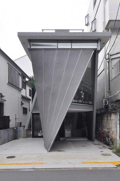 室内だけでなく外観も特徴づける傾斜した曲面壁。左右に1台ずつの駐車スペースがある。