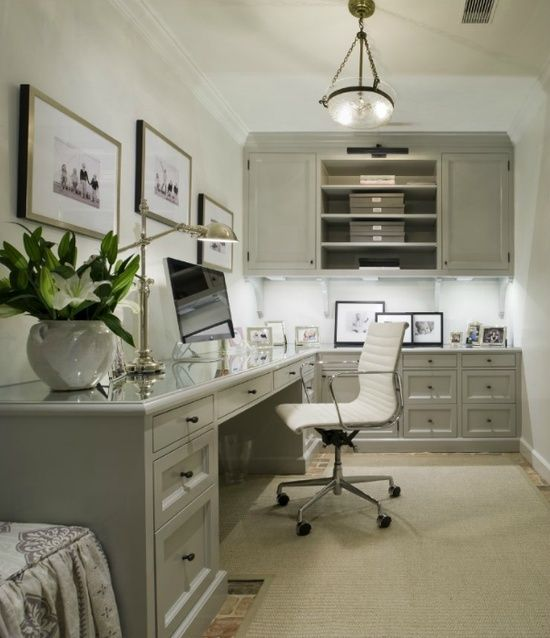 Great Modern Home Office Design Idea. Gray office with L shaped desk with beveled top with white Eames Management Chair. Gray built-in office cabinets with glossy gray cabinet moldings. Desk with polished nickel pharmacy lamp, computer and framed photos. Gray bound sisal rug over brick office floor.