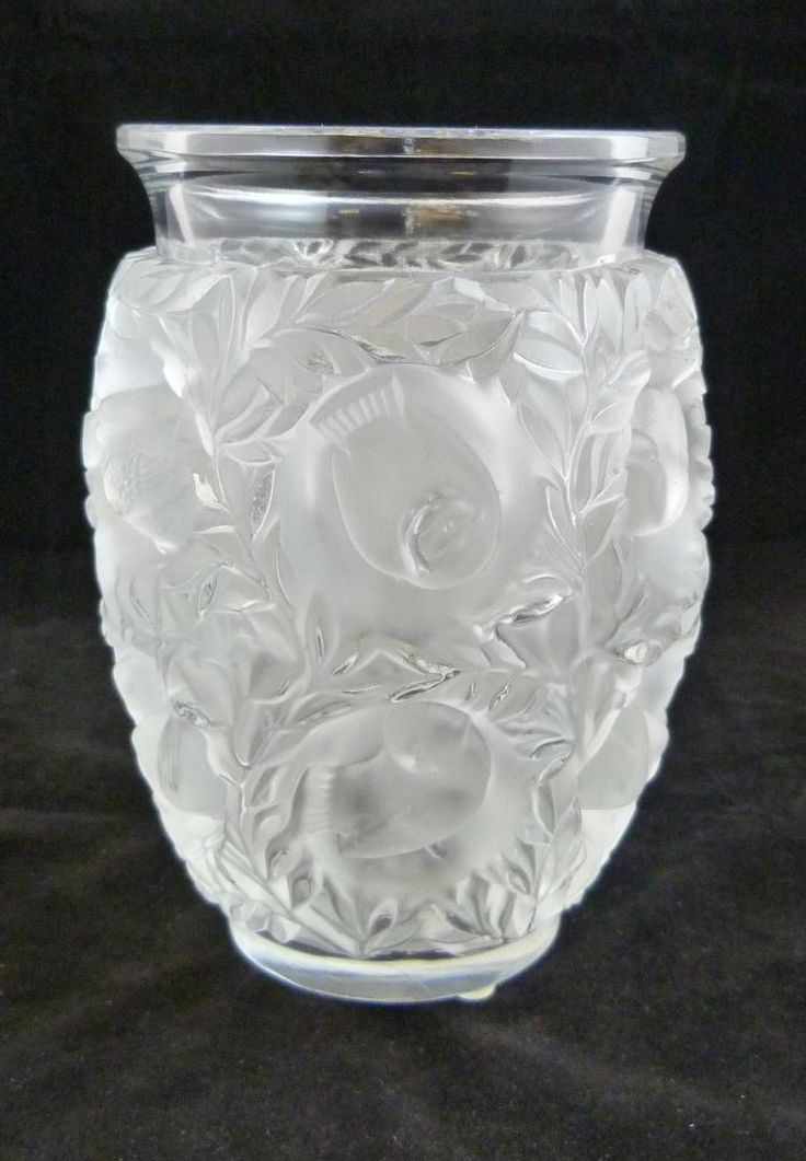The epitome of romance, this Lalique Bagatelle Vase is draped with deep set lovebirds and springtime foliage. This stunning piece features a repeated relief sculptural bird motif surrounded by swirling decorative leaf accents. Made in France.