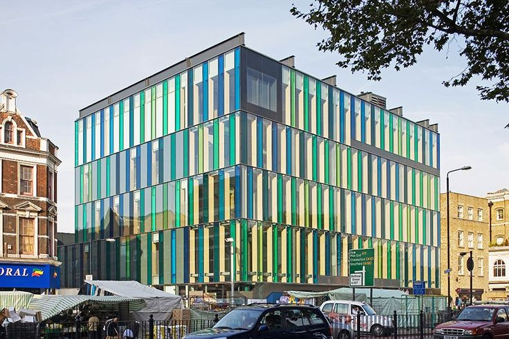 David Adjaye's Idea Store in London boasts a glass façade that mimics the neighborhood's nearby market stalls, whose structures are draped with green-and-blue-striped fabrics.