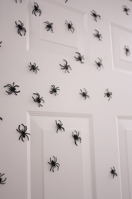 """Glue magnets to the back of spiders and put on front door. I bought about a hundred plastic spiders from the target cheap-o section for $2.50. Then I got magnet """"tape"""" from Joann Fabric for 80 cents. Hot glued the tape to the back of the spiders and voila! Really creepy halloween door. These babies are going to be scattered around our halloween wreath on the front door this year!"""