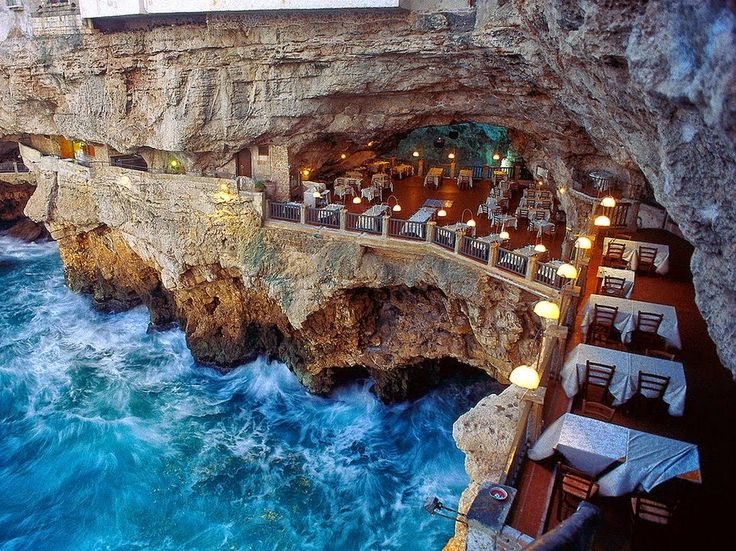In the town of Polignano a Mare in southern Italy (province of Bari, Apulia), lies a most unique dining experience at the Grotta Palazzese. Open only during the summer months, a restaurant is created inside a vaulted limestone cave, looking outwards toward the sea. The restaurant is part of the Grotta Palazzese hotel located above.