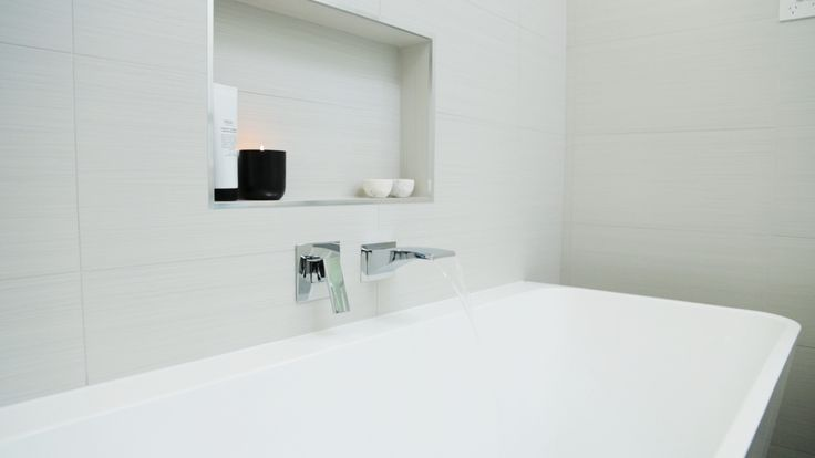 This full bathroom renovation transformed the room into a modern masterpiece. Great interior design with all the latest bathroom products from Highgrove Bathrooms. Waterfall bath spout and in wall mixer over freestanding back to wall bath. A niche is a great way of showing open storage.