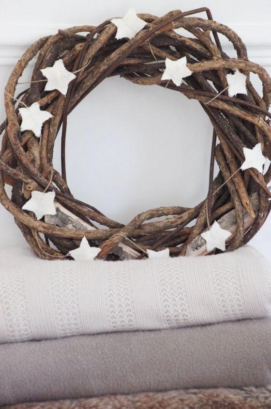 Guirlande d'étoiles taillées dans une toile blanche rustique, sur une couronne de noisetier.