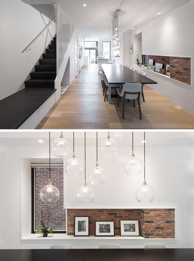 Inside this renovated home, the interior has been brightened up with bright white walls and a light colored wood floor. A glimpse of the original brick wall has been incorporated into a small shelving nook beside the dining table.