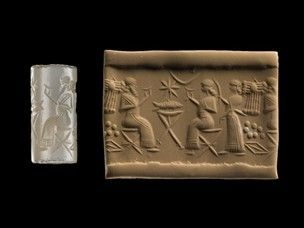 Grey-blue chalcedony cylinder seal; two figures sit on camp stools facing each other and raising shallow cups, on either side of a cross-legged table which has bull's legs; on the table lies a fish and above a star and a crescent; behind the figure on the right stands an attendant with a fly-whisk, and behind the attendant are a winged disc, the Pleiades and a rhomb. All three figures have indentical shoulder-length hairstyles and wear wide-belted robes with a fringe round the hem, lines…