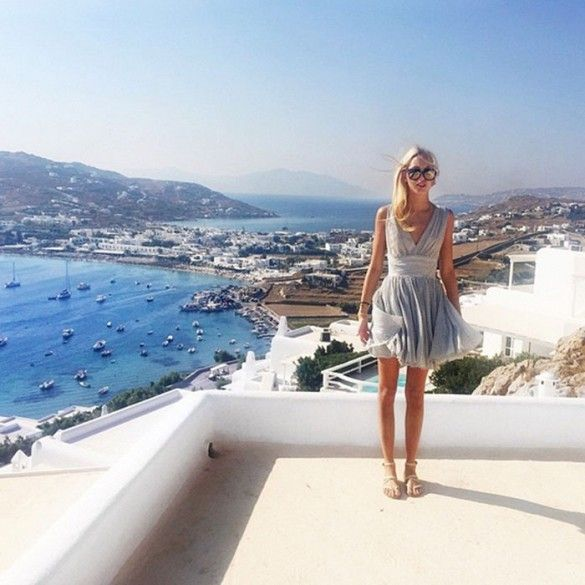 Princess Olympia of Greece wears a grey chiffon dress with a v neckline, gladiator sandals and sunglasses.