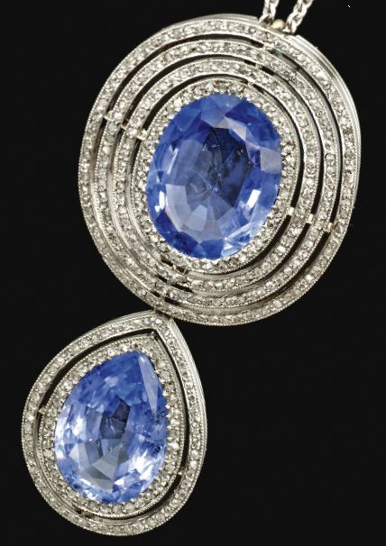 A sapphire and diamond brooch/pendant, early 20th century. The oval sapphire surmount within pierced concentric surrounds millegrain-set with rose-cut diamonds, suspending a pear-shaped drop similarly set, mounted in platinum, on a later white gold curb link chain, fitted case by Peter Rath, Hof Juwelier, München.
