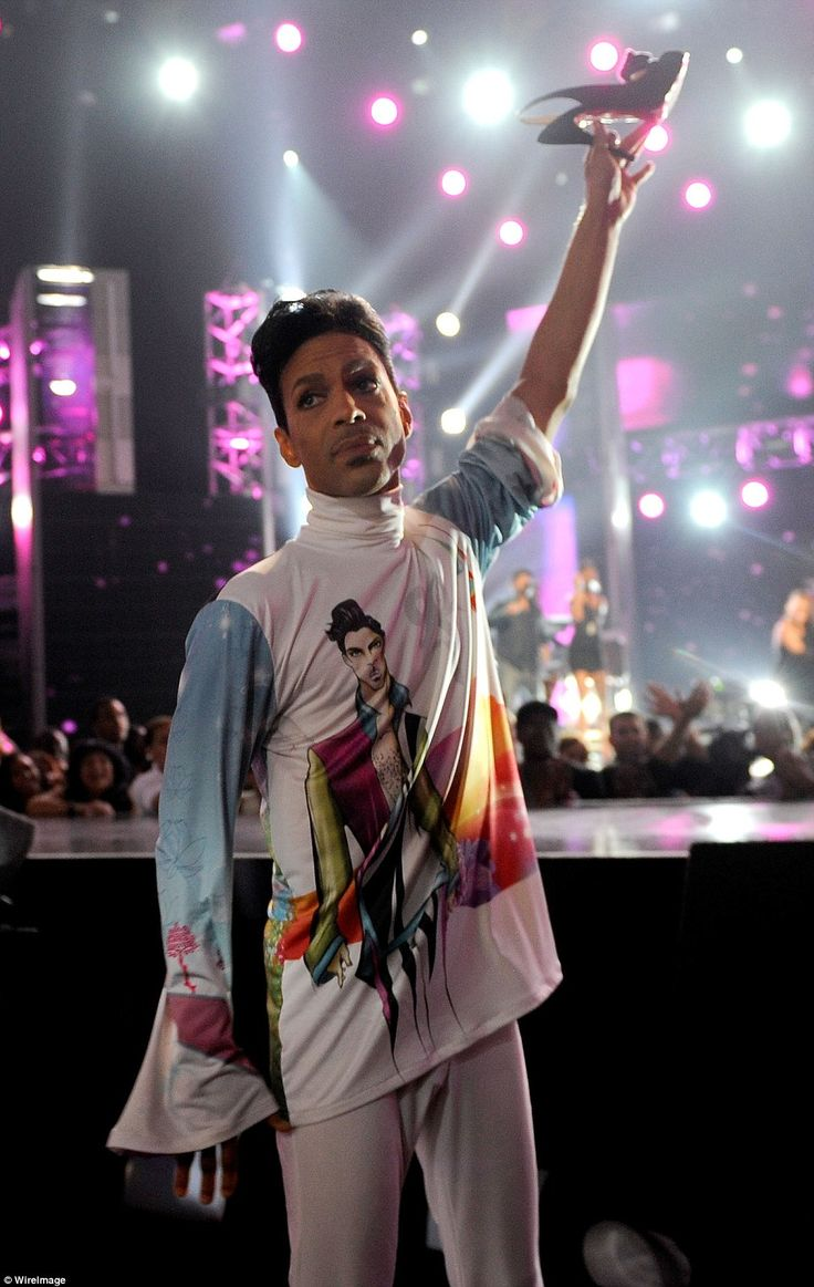 Prince holds up singer Patti LaBelle's shoe during her performance at the 2010 BET Awards ...