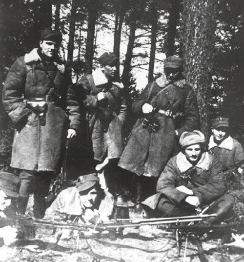 """Od lewej stoją: Edward Dziemianowicz """"Czarny""""; Henryk Łapiński """"Szary"""", Eugeniusz Godlewski """"Topór"""", siedzą: kpt. Kazimierz Kamieński """"Huzar""""; za nim Wacław Dziemianowicz """"Góral""""; leżą od lewej: Lucjan Niemyjski """"Krakus"""" i Jerzy Walukiewicz """"Fryc""""."""