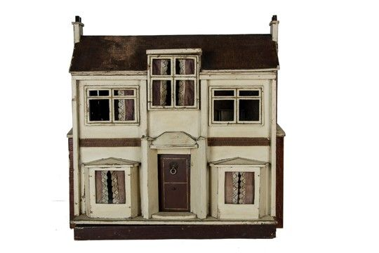 A G & J Lines Dolls' House, cream-painted with gold lining, central brown front door with lion head knocker, bay window either side, central dormer window, printed paper tiled roof and brick sides, front opening to reveal four rooms, hall, stairs and landing, original papers and fireplace, 1920s --28in. (71cm.) wide (some wear and ageing)