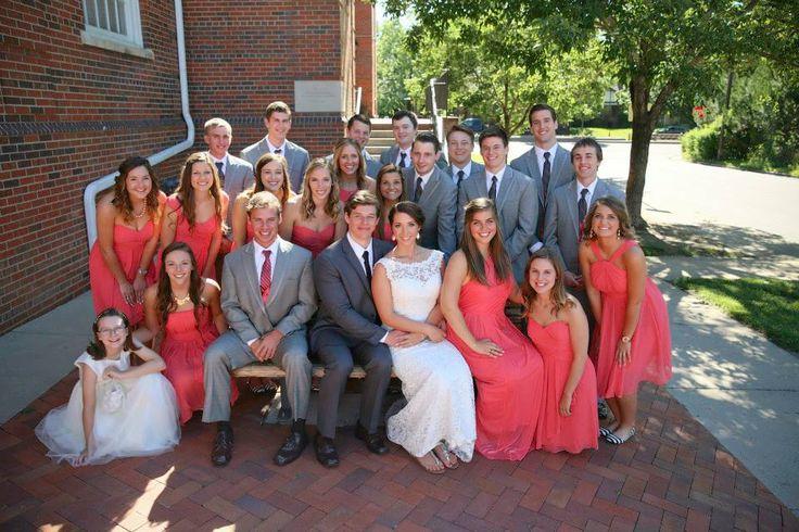 22 people wedding party. Guava bridesmaid dresses. Gray groomsmen tuxes.