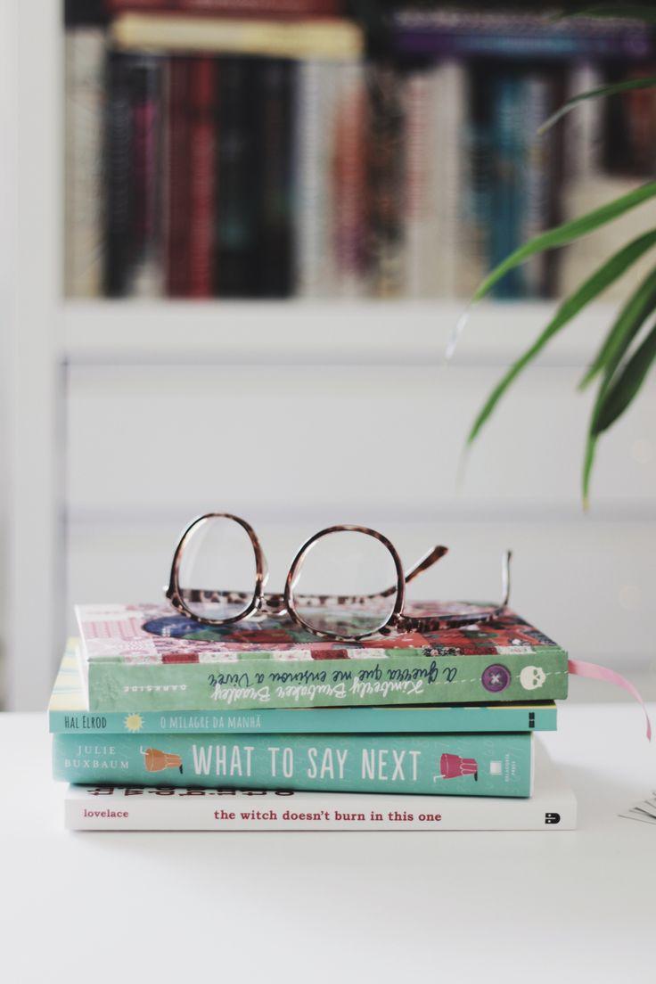 Livros que estou lendo no momento: jovem adulto, desenvolvimento pessoal e poesia moderna.  Livros em cima da mesa com estante de livros ao fundo.  #melinasouza #books #livros