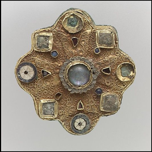 Disk Brooch  Date: second half 7th century Culture: Frankish Medium: Gold sheet, filigree, moonstone/adularia, glass cabochons, garnets, mother-of-pearl, and moonstone Dimensions: Overall: 2 5/16 x 3/4 x 2 5/16 in. (5.8 x 1.9 x 5.8 cm) Classification: Metalwork-Gold Credit Line: Gift of J. Pierpont Morgan, 1917