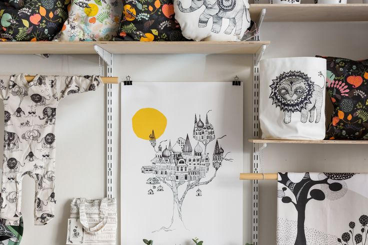 Close-up on one of our walls in the studio shop. Poster Another Birdsnest, basket Lion, various cushions and a baby clothing colab created with kids brand UNI.