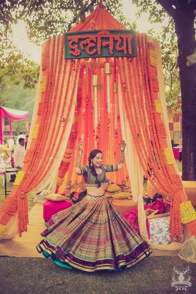 Printed mehendi lehenga , twirling bride , genda flower decor