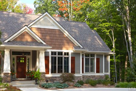 The latest color trend for home exteriors includes darker shades of paint or siding, such as this house with Mastic Home Exteriors siding by Ply Gem Quest in Woodland Green.