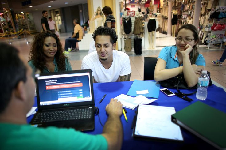 Ashante Thurston, John Riascos and Julieth Riascos speak with an insurance agent about purchasing insurance under the Affordable Care Act at a kiosk setup at the Mall of Americas on Dec. 11, 2013 in Miami, Florida. (Photo: Joe Raedle/Getty)