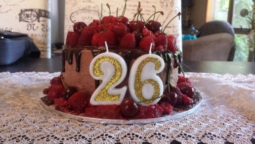 Midnight chocolate cake with raspberry filling covered in fresh  raspberries, strawberries and cherries all covered in chocolate swiss meringue icing