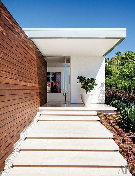 The front entrance features a pivoting glass door | archdigest.com