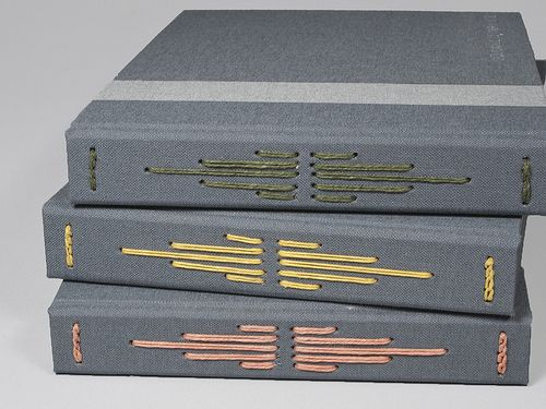 Custom Wedding Guest Books by White Sparrow Bindery.  Shown in Slate Gray with Pine, Yellow, and Terra Cotta thread.