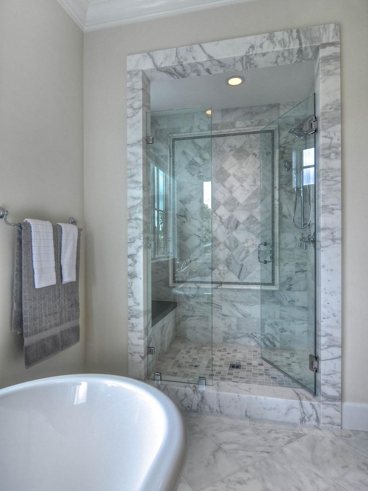 This bathroom features a soaking bathtub and walk-in shower with glass doors and bench. Mosaic tile creates the look of artwork in the sleek shower.
