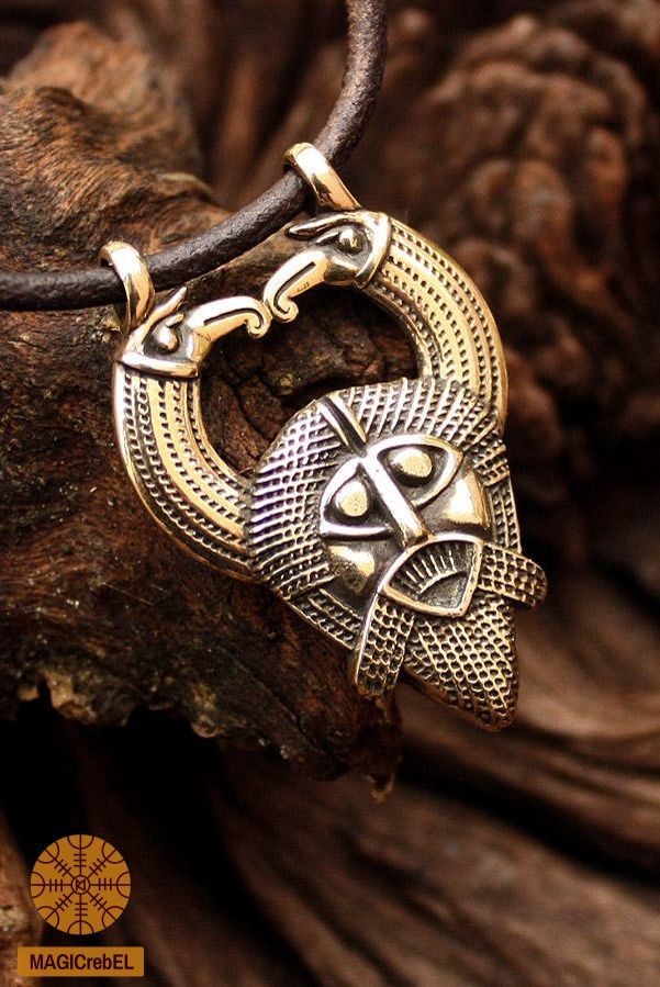 The pendant features Norse god Odin on the front side. The two raven heads at each side of the pendant represent Huginn and Muninn. On the flip side the pendant is the rune Gar, or Gungnir symbol which means spear, specifically Odin's Spear.  #magicrebel #bronze #odin #huginn #muninn #ravens #gungnir #rune #gar #spear #pendant #necklace