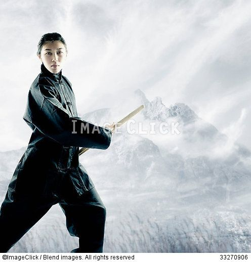 RF 33270906 Portrait of a young woman holding a wooden stick standing in a martial arts stance :: ImageClick